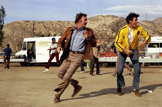 Full shot of Gene Hackman as Harry Moseby and Anthony Costello as Marv Ellman playing football.