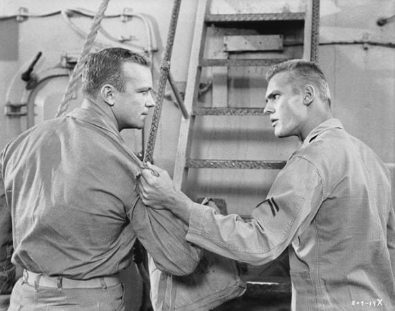 Medium shot of Tab Hunter as Danny Forrester grabbing sleeve of Aldo Ray as Andy Hookens.