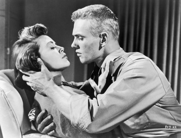 Medium shot of Tab Hunter as Danny Forrester about to kiss Dorothy Malone as Elain Yarborough.