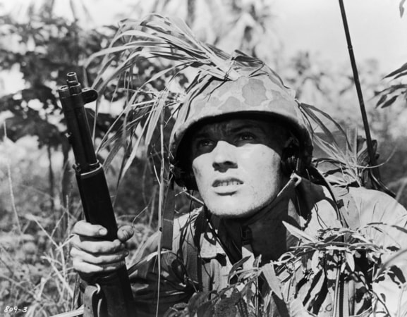Medium shot of Tab Hunter as Danny Forrester, wearing helmet and holding gun/rifle.