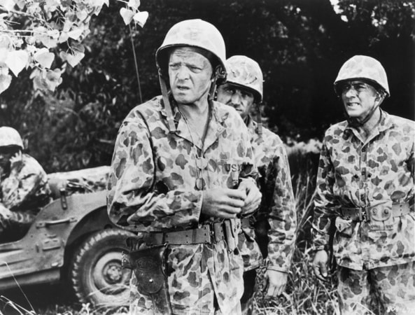 Medium shot of Van Heflin as Sam 'Highpockets' Huxley, James Whitmore as Mac, and soldier, all wearing camouflage and helmets.