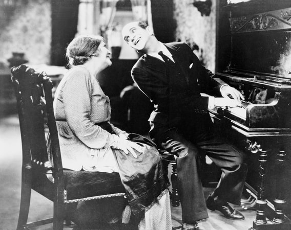 "Full shot of Al Jolson as Jakie Rabinowitz seated at piano singing to Eugenie Besserer as Sara Rabinowitz during musical number ""Blue Skies""."