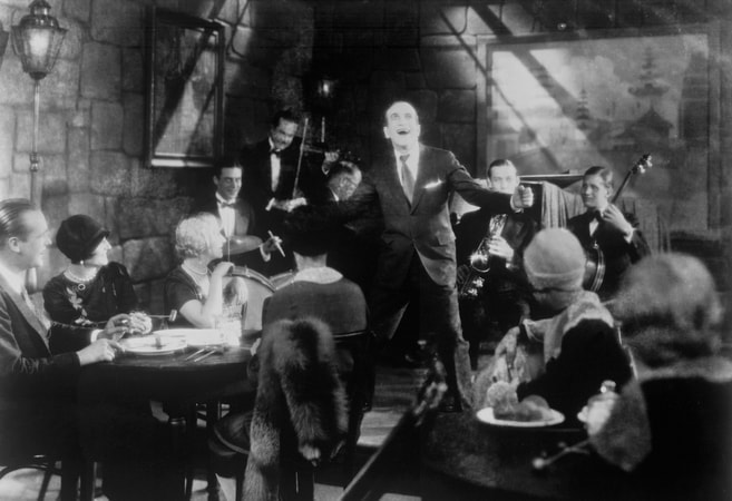 "Full shot of cafe patrons listening to Al Jolson as Jakie Rabinowitz singing and orchestra playing during musical numbers ""Dirty Hands, Dirty Face"" and ""Toot, Toot, Tootsie""."