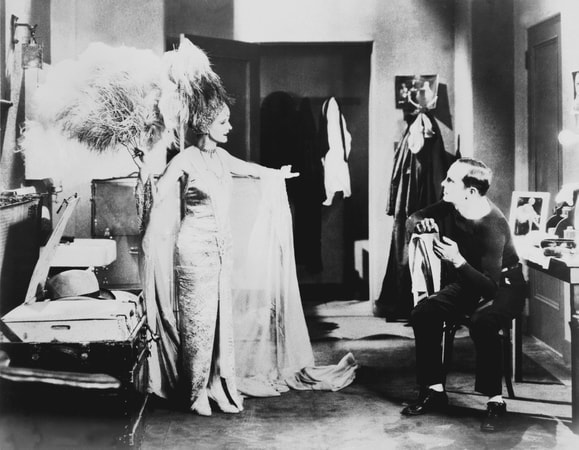 Full shot in dressing room of May McAvoy as Mary Dale facing seated Al Jolson as Jakie Rabinowitz.