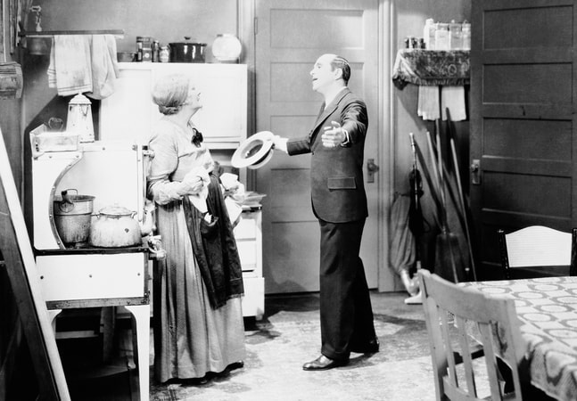 Full shot of Al Jolson as Jakie Rabinowitz, holding hat, with arms outstretched to Eugenie Besserer as Sara Rabinowitz.