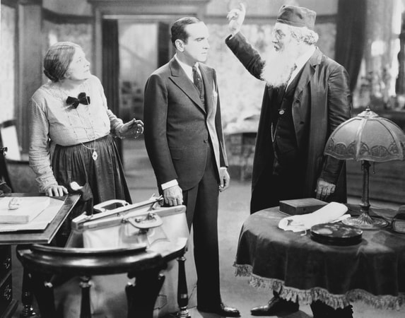 Full shot of Warner Oland as The Cantor admonishing Al Jolson as Jakie Rabinowitz while Eugenie Besserer as Sara Rabinowitz looks on.