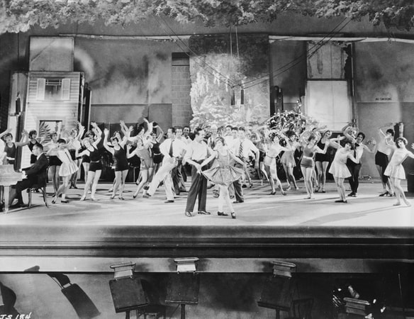 Wide shot of stage with Al Jolson as Jakie Rabinowitz and May McAvoy as Mary Dale in front of rehearsing chorus.