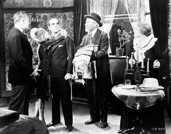 Full shot of May McAvoy as Mary Dale embracing Al Jolson as Jakie Rabinowitz while man holding shawl, Eugenie Besserer as Sara Rabinowitz, and other man look on.