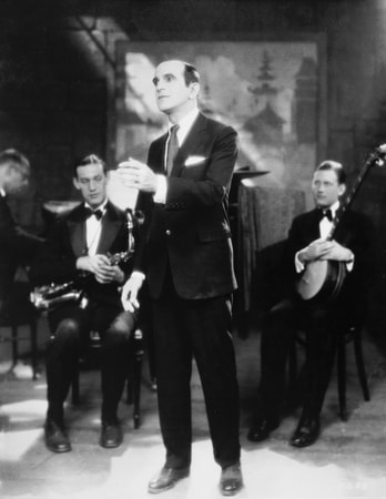 "Full shot of Al Jolson as Jakie Rabinowitz singing ""Dirty Hands, Dirty Face"" in front of band."