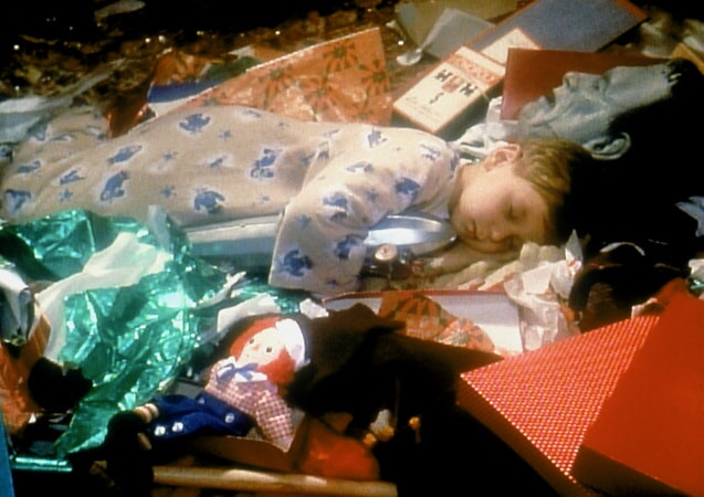 Randy asleep in a heap of wrapping paper and presents