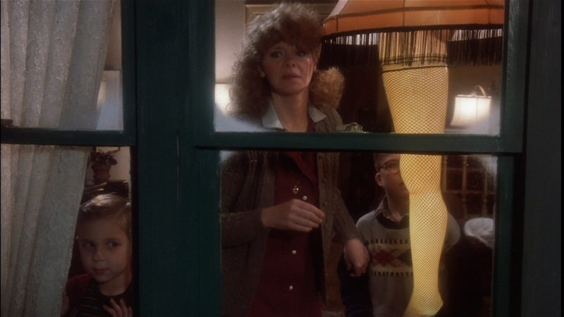 Mrs. Parker, Randy and Ralphie looking out window with leg lamp lit