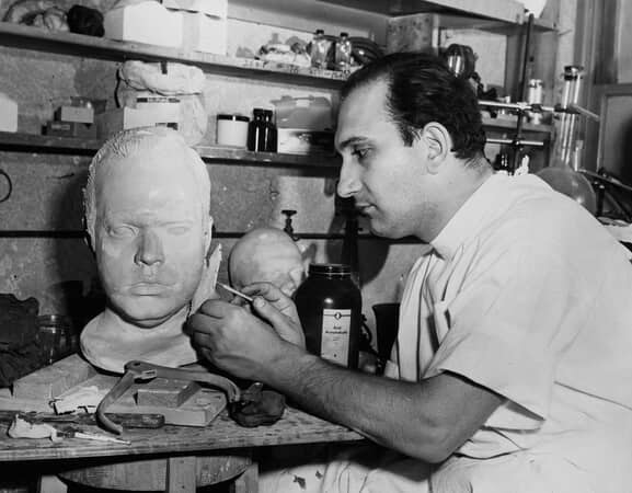 BTS shot of makeup artist Maurice Seiderman working on a plaster face cast of Orson Welles as Charles Foster Kane.