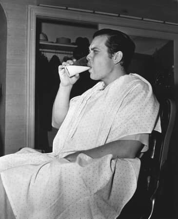 BTS shot of director Orson Welles as Charles Foster Kane drinking glass of milk.
