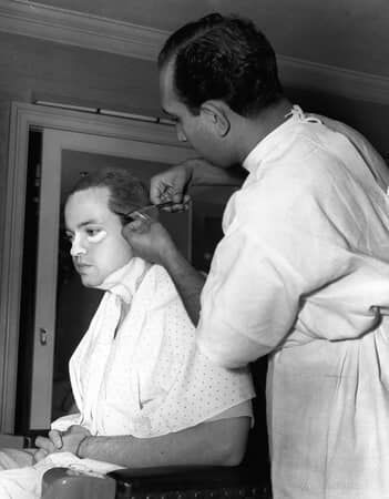 BTS shot of Orson Welles as Charles Foster Kane having a hair piece applied by makeup artist Maurice Seiderman.