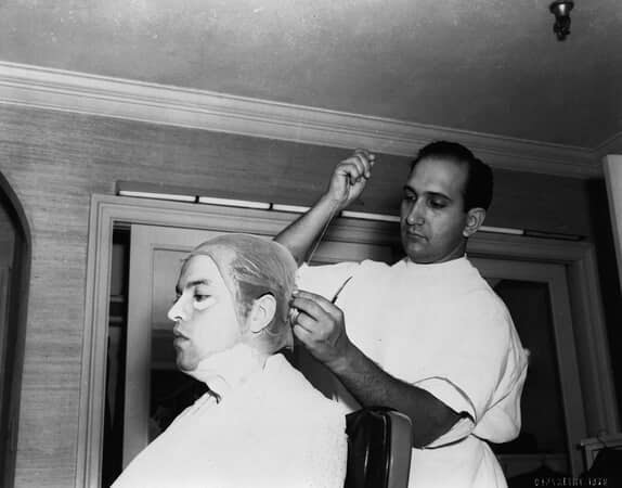 BTS shot of Orson Welles as Charles Foster Kane having a plastic cap/hat sewn on his head by makeup artist Maurice Seiderman.