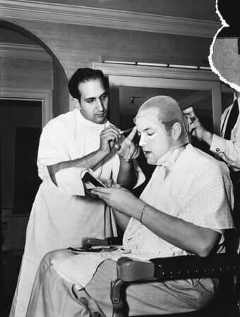 Medium BTS shot of makeup artist Maurice Seiderman applying makeup to director Orson Welles as Charles Foster Kane.