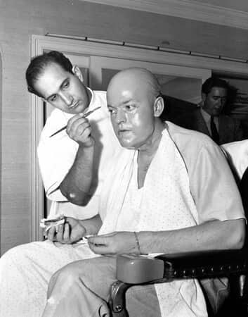 BTS shot of makeup artist Maurice Seiderman applying makeup to Orson Welles as Charles Foster Kane.