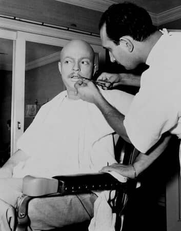 BTS shot of Orson Welles as Charles Foster Kane having a mustache applied by makeup artist Maurice Seiderman.