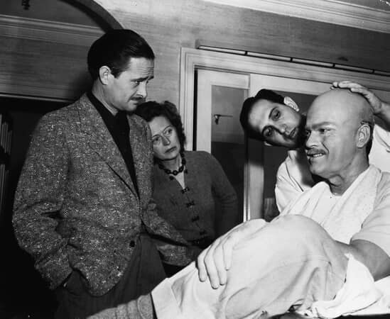 Medium BTS shot of cinematographer Gregg Toland; woman looking at makeup artist Maurice Seiderman applying makeup to Orson Welles as Charles Foster Kane.