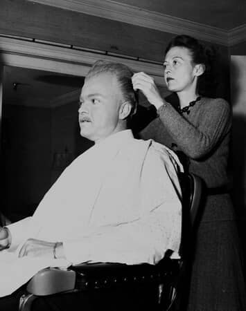Medium BTS shot of Orson Welles as Charles Foster Kane, his hair being combed by woman.