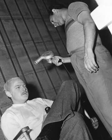 BTS shot of makeup artist Maurice Seiderman aiming hairdrier at Orson Welles as Charles Foster Kane.