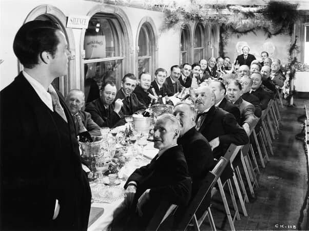 Orson Welles as Charles Foster Kane, looking at group of men seated at long banquet table.