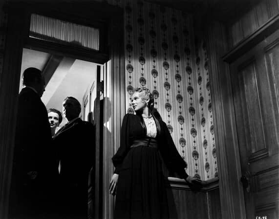 Medium shot of Orson Welles as Charles Foster Kane, Ruth Warrick as Emily Norton Kane, and Ray Collins as Boss James 'Jim' W. Gettys, standing in doorway; with Dorothy Comingore as Susan Alexander leaning against wall.