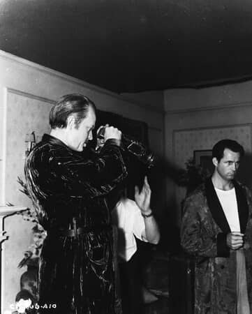BTS shot of director Orson Welles as Charles Foster Kane, looking through test viewfinder with film crew.