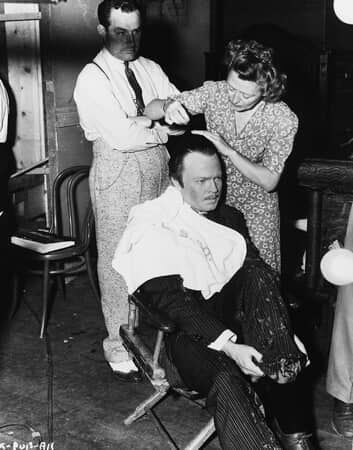 BTS shot of director Orson Welles as Charles Foster Kane, having his hair combed by woman, as man observes.