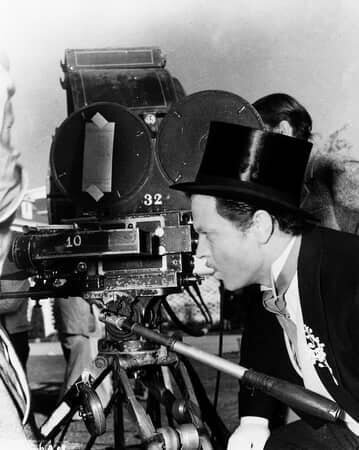 BTS shot of director Orson Welles as Charles Foster Kane wearing top hat and tuxedo, looking through camera lens.