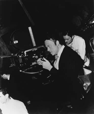 BTS shot of director Orson Welles as Charles Foster Kane looking through camera lens with cinematographer Gregg Toland.
