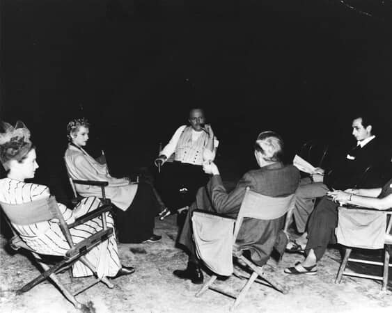 BTS shot of director Orson Welles as Charles Foster Kane, smoking pipe surrounded by film crew.