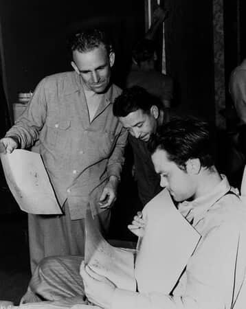 BTS shot of two men showing renderings to director Orson Welles.