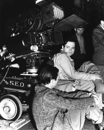 BTS shot of cinematographer Gregg Toland (back to camera) and director Orson Welles; with film crew and camera in background.