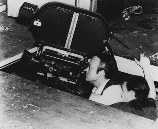 BTS shot of director Orson Welles a Charles Foster Kane and cinematographer Gregg Toland, looking through camera; a hole in soundstage floor had to be cut to accommodate camera.