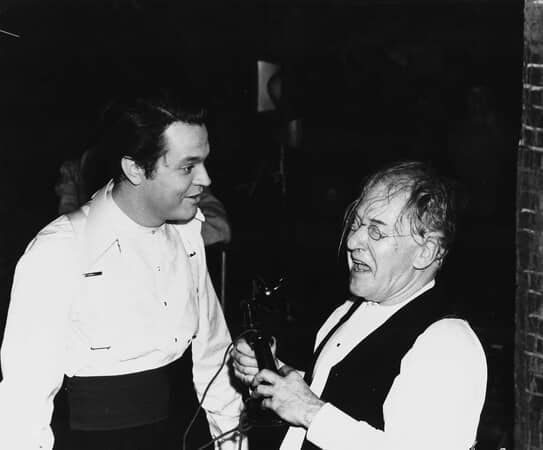 BTS shot of director Orson Welles as Charles Foster Kane and a laughing Erskine Sanford as Herbert Carter.