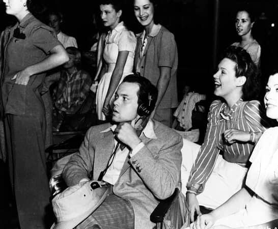BTS shot of director Orson Welles wearing headphones, with film crew.
