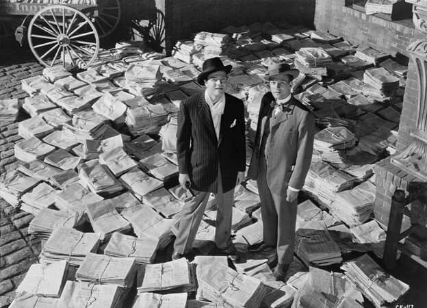 High-angle shot of Orson Welles as Charles Foster Kane and Joseph Cotten as Jedediah Leland, surrounded by bundled newspapers.