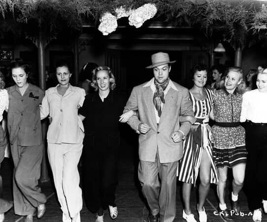 BTS shot of group of women and director Orson Welles, running.