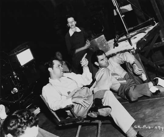 BTS shot of director Orson Welles, smoking pipe and pointing, with assistant director Eddie Donahoe and other film crew members.