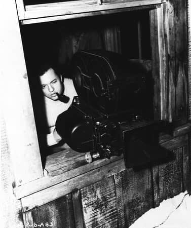 BTS shot of director Orson Welles, behind camera.