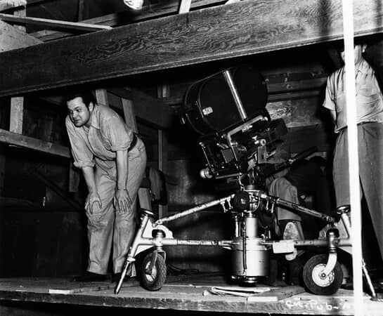 BTS shot of director Orson Welles and cinematographer Gregg Toland (face not visible), with camera.