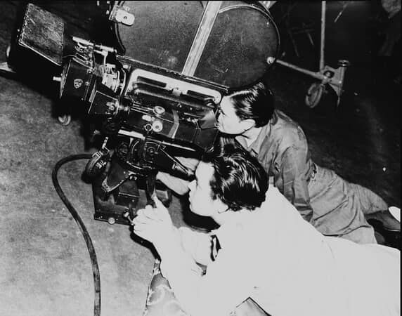 BTS shot of director Orson Welles and cinematographer Gregg Toland, looking through camera mounted to floor.