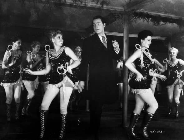Full shot of Orson Welles as Charles Foster Kane, looking at Joan Blair as Georgia, while other women dance around them.