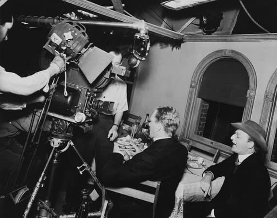 BTS shot of Joseph Cotten as Jedediah Leland and Everett Sloane as Bernstein sitting at dining table as film crew with camera prepare for shoot.
