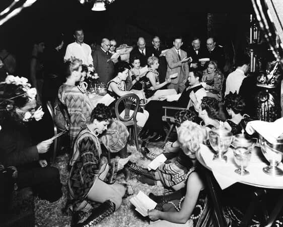 BTS shot of Orson Welles as Charles Foster Kane sitting and looking at Joseph Cotten as Jedediah Leland both surrounded by female dancers in costume.