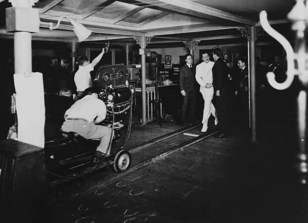 BTS shot of cinematographer Greg Toland, behind camera, filming director Orson Welles as Charles Foster Kane, talking to men.