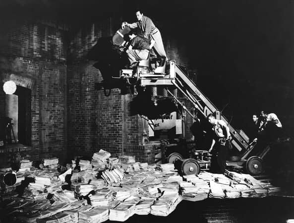 BTS shot of cinematographer Gregg Toland, and director Orson Welles who plays Charles Foster Kane, on camera crane, filming bundled newspapers below, with film crew pushing crane dolly.