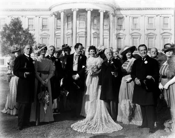 Full shot of wedding of Orson Welles as Charles Foster Kane and Ruth Warrick as Emily Norton Kane with guests in front of White House.