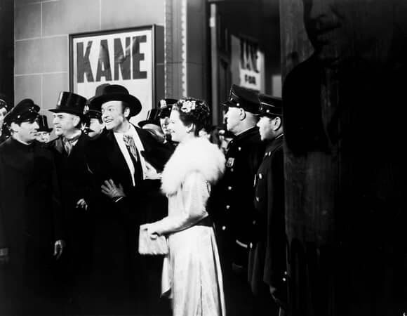 Long shot of Orson Welles as Charles Foster Kane, Sonny Bupp as Kane III, and Ruth Warrick as Emily Norton Kane; with policemen and people.